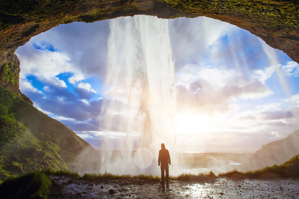 person in front of waterfall along the ring road in iceland