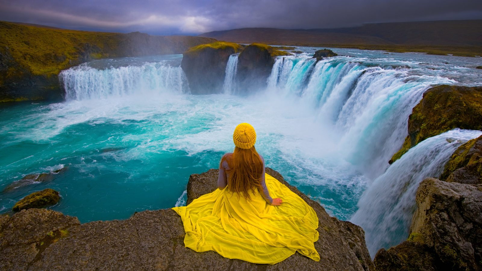 Victoria Yore Sitting at Godafoss waterfall in iceland
