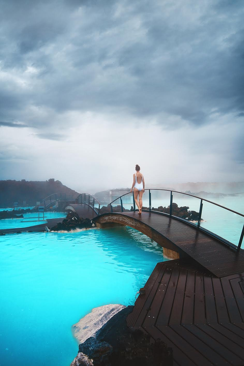 woman walking on a bridge across blue water at the blue lagoon. she is wearing a white bathing suit