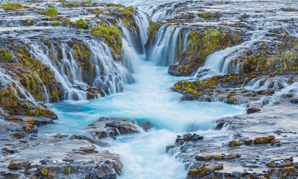 Bruarfoss waterfall with pristine blue water flowing over mossy green rocks