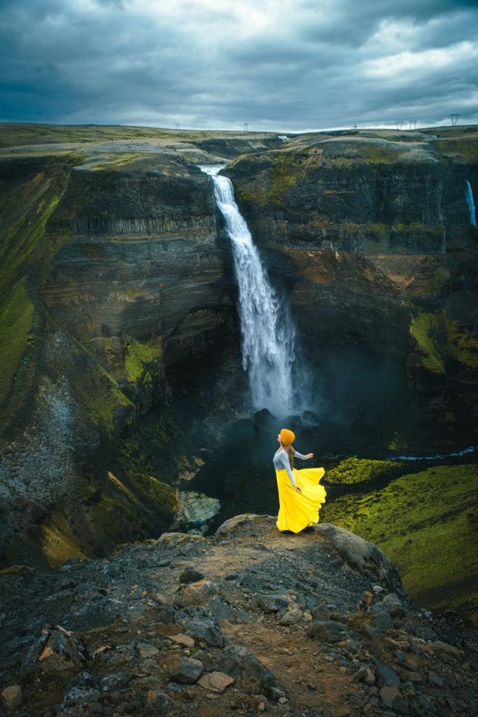 woman in yellow skirt standing on top of a mountain with Haifoss waterfall in the background