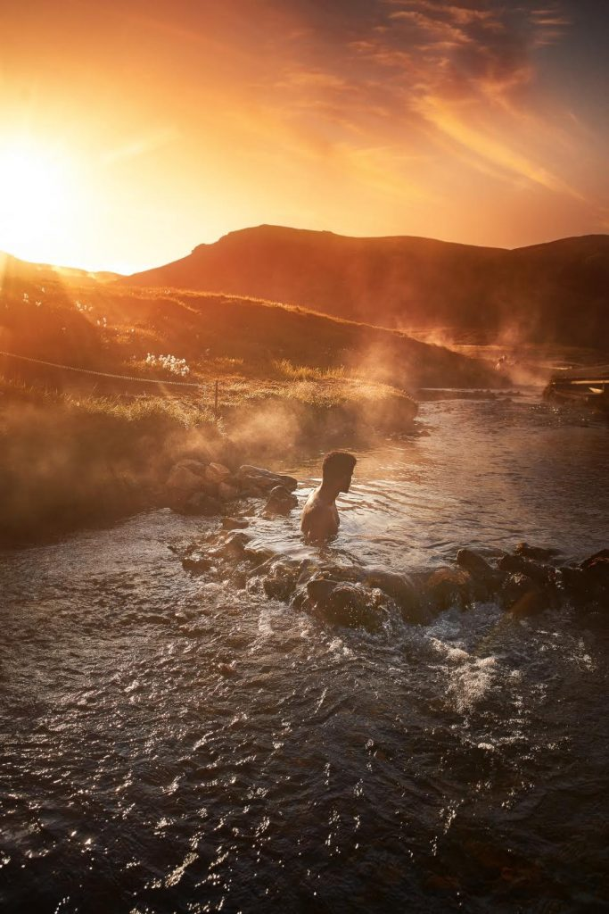 man sitting in a river with steam coming up at sunset. the river is named Reykjadalur Hot Springs in iceland