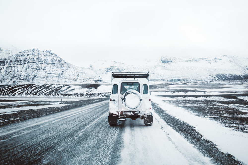 car driving on iceland's ring road in winter with snow and ice covering the mountains