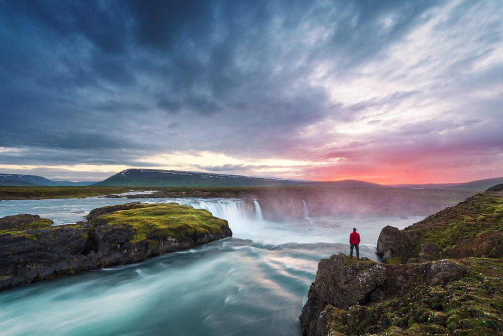 person standing at Godafoss Waterfall