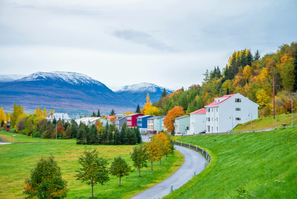 Photo of Akureyri Icleand featuring some colorful apartment homes. Lush landscape and a mountain in the background.