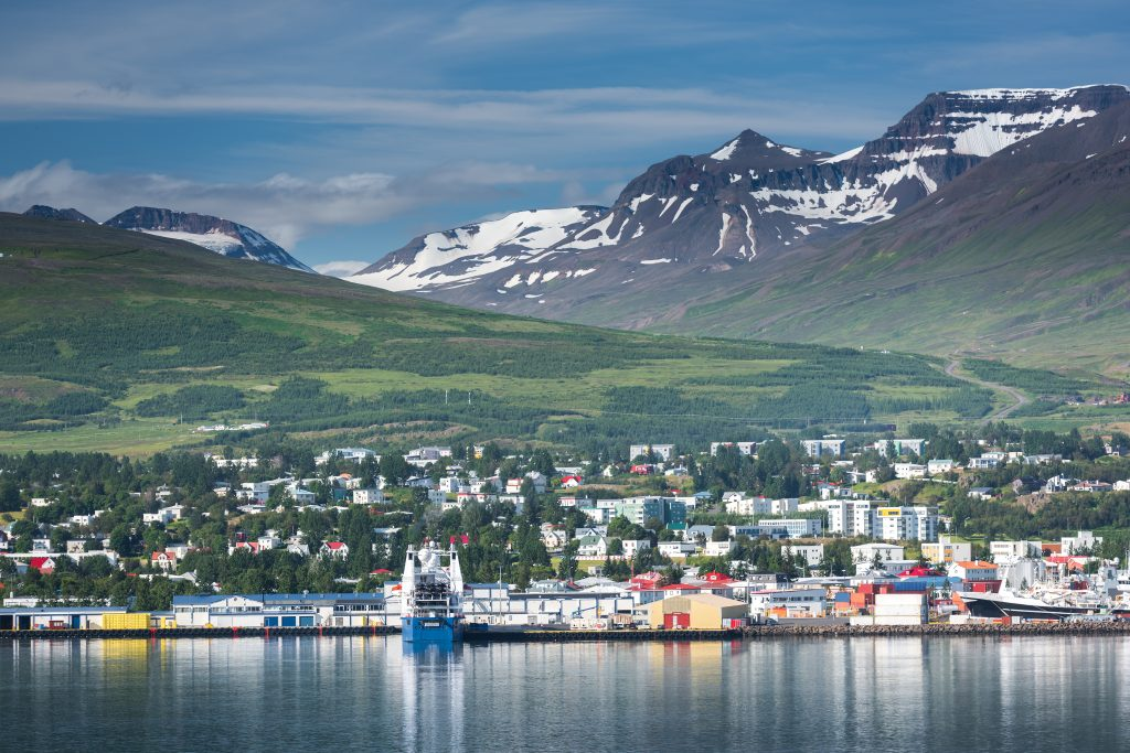 Photo of the town of Akureyri Icleand. Mountains are seen in the background with many homes and buildings scattered in the foreground.