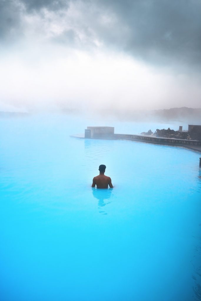 man standing in bright blue waters of blue lagoon