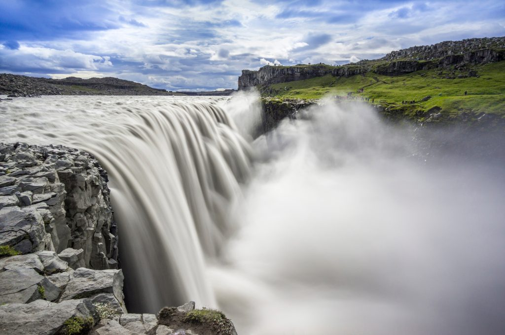 a wide powerful waterfall ending a cloud of billowing mist best things to do in Iceland