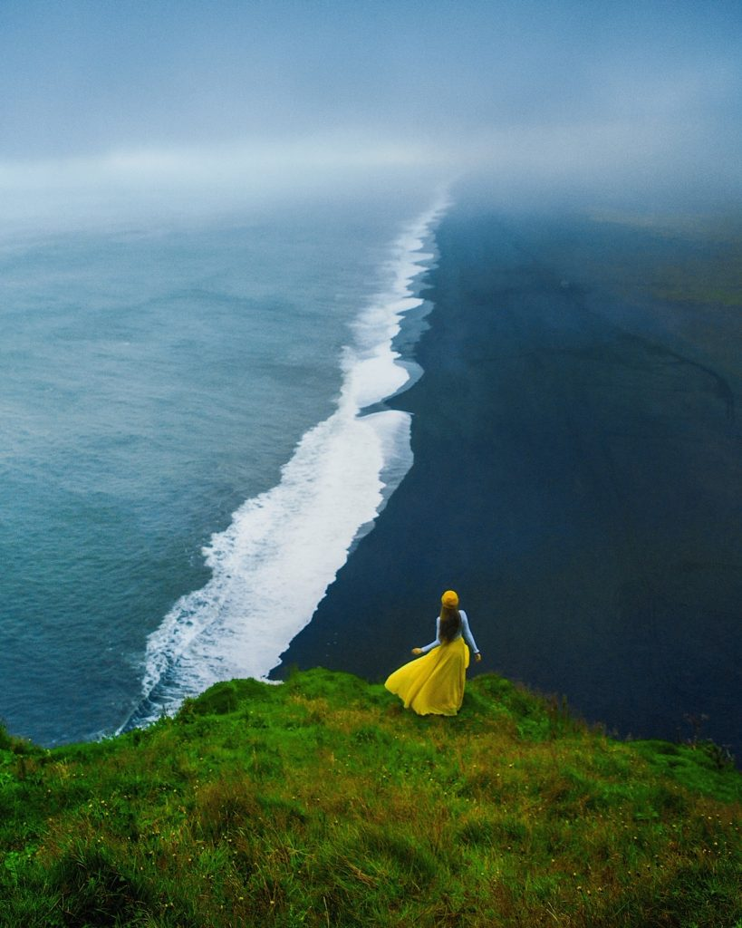 woman in yellow overlooking black sand beach from viewpoint best things to do in Iceland