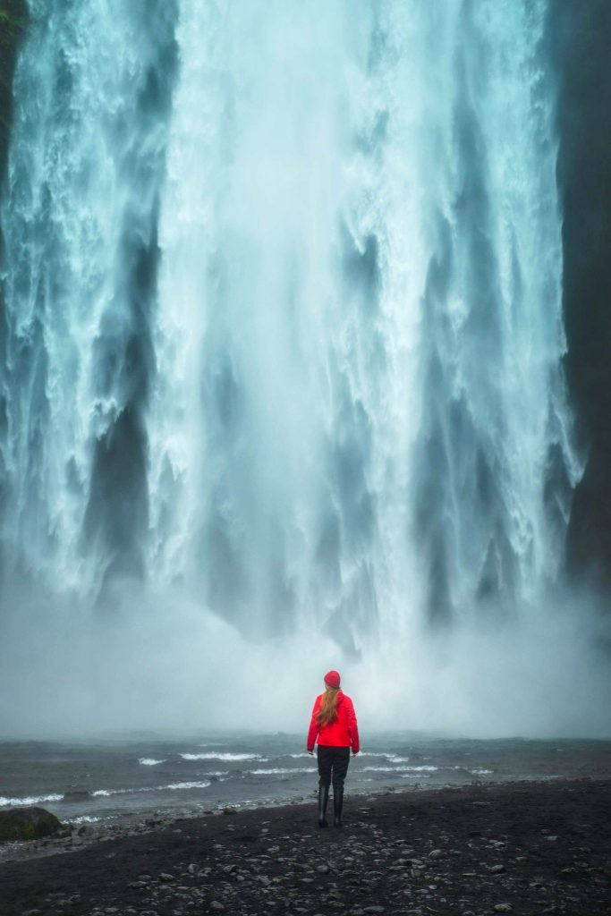 woman in red at the base of a powerful waterfall best things to do in Iceland