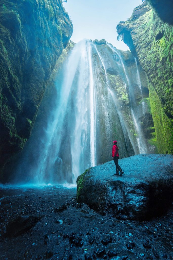 person in red raincoat standing at base of waterfall best things to do in Iceland