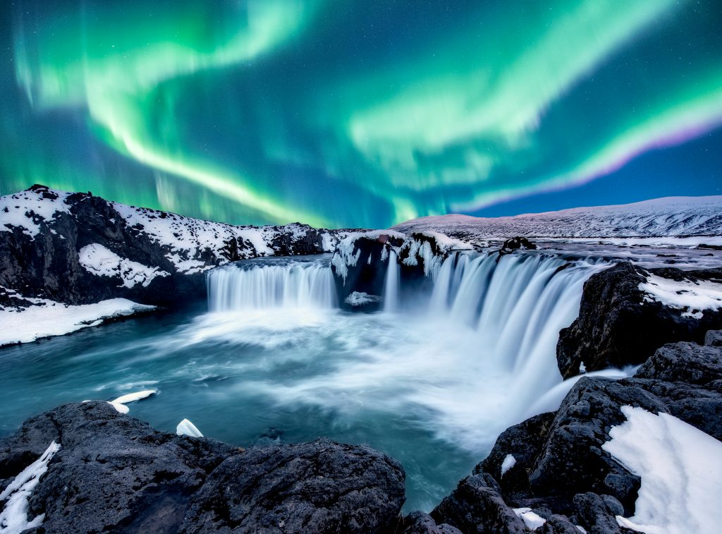 snow covered semi circle waterfall with Northern Lights