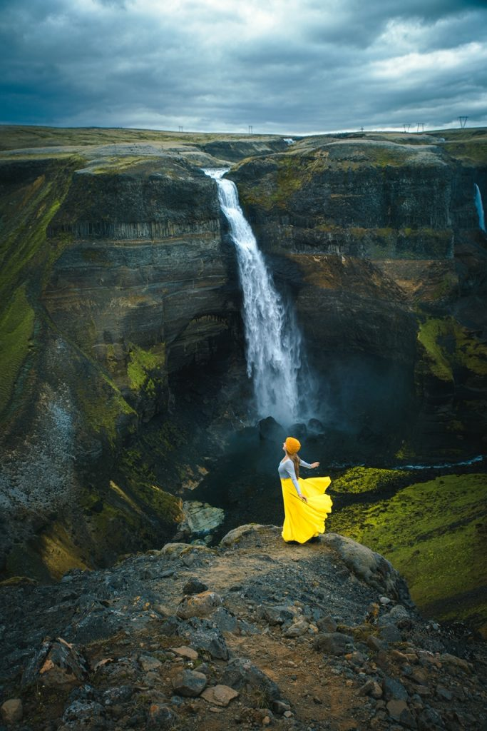 woman in yellow skirt in front of Haifoss waterfall best things to do in Iceland