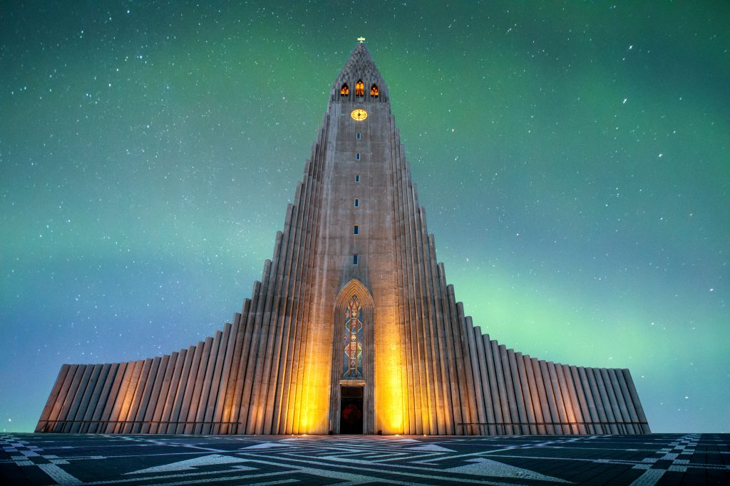 towering church framed by Northern Lights best things to do in Iceland
