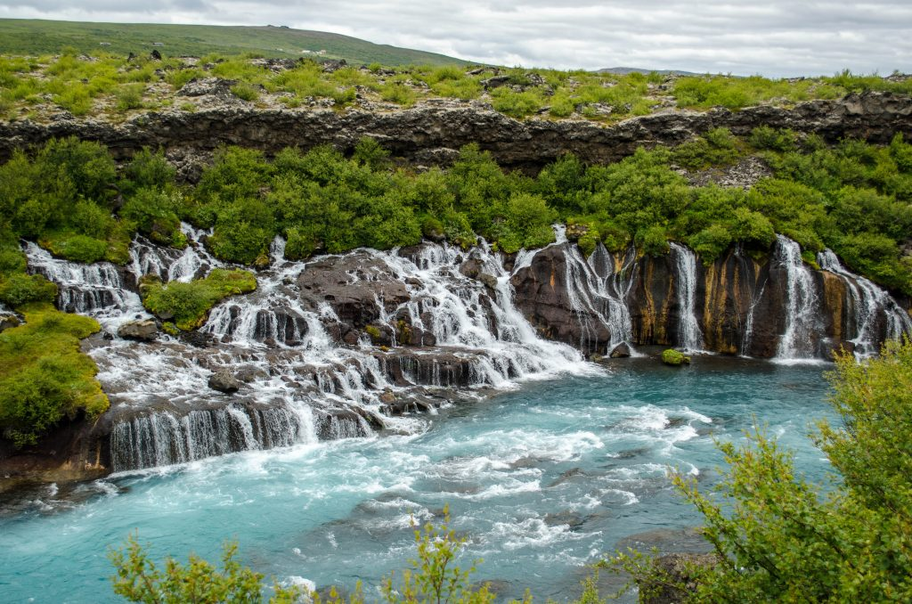 shallow lacy waterfall surrounded by greenery and ending in turquoise pool