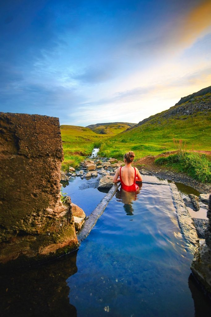 woman sitting in Hrunalaug hot springs best things to do in Iceland