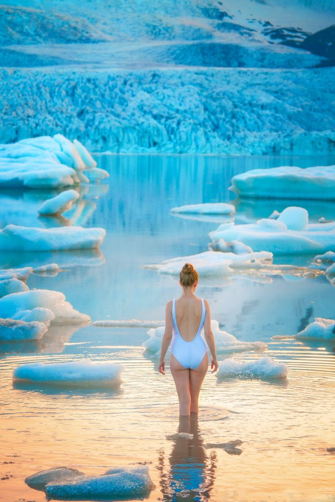 woman wading in Jokulsarlon glacier lagoon best things to do in Iceland