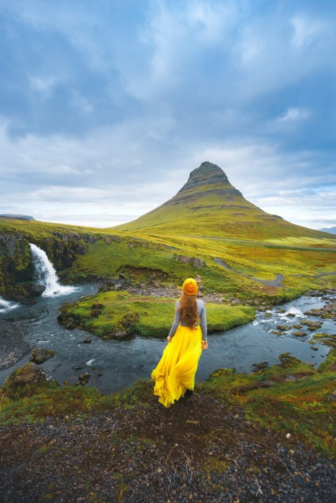 woman in yellow in front of Kirkjufell Mountain best things to do in Iceland