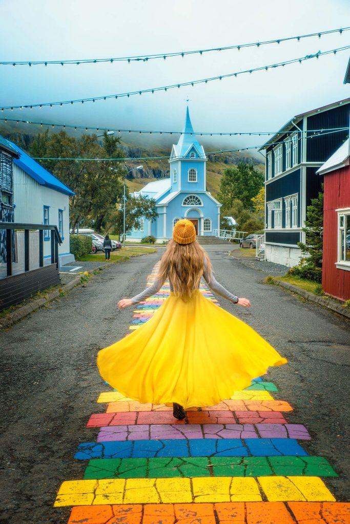 woman in yellow skipping down rainbow street to blue church