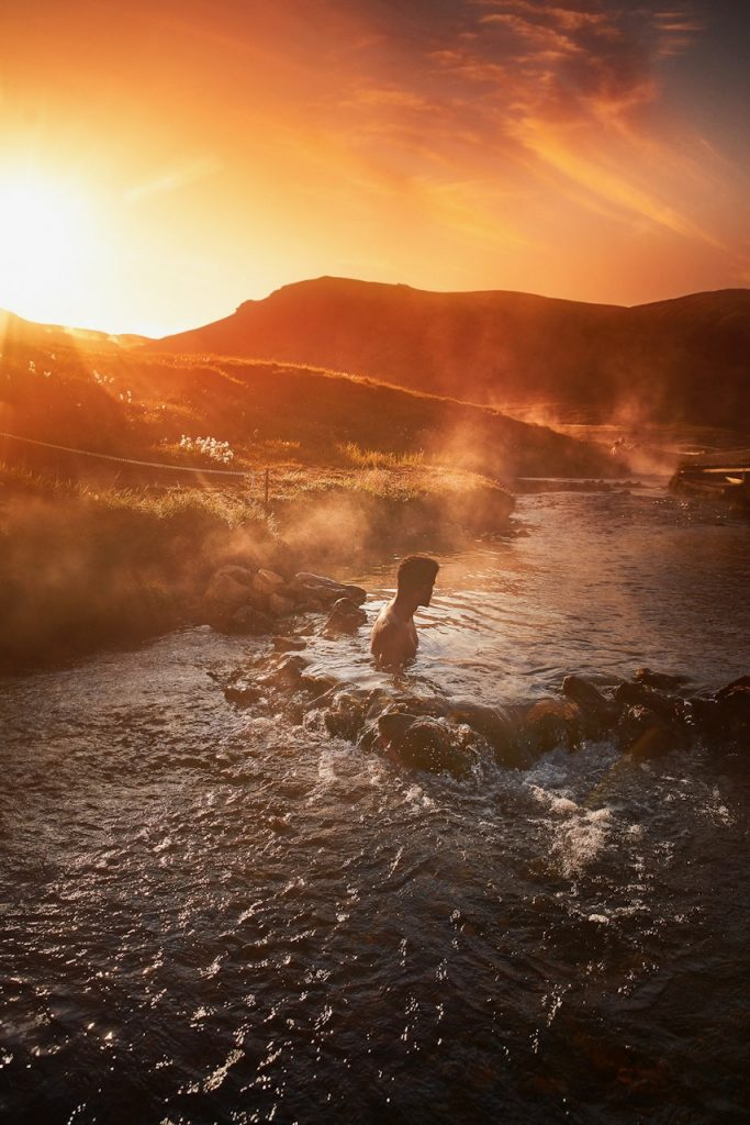 man sitting in river hot spring during golden hour best things to do in Iceland