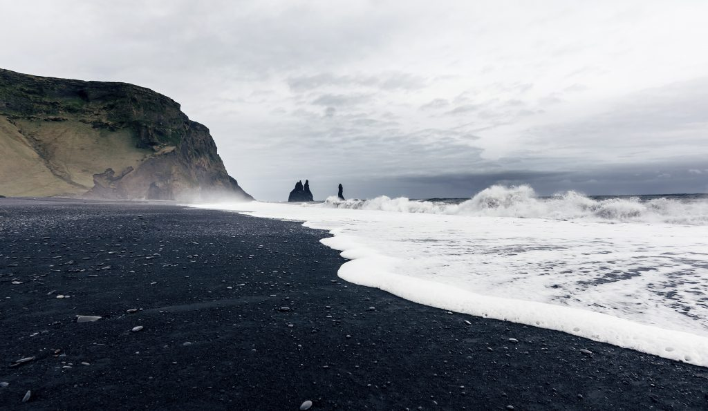 black sand beach with rock formations in the distance