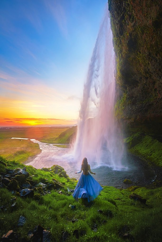woman in blue skirt near cascading waterfall at sunset