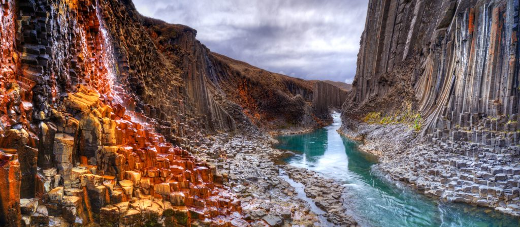 teal river flowing through gray, red, and orange basalt columns best things to do in Iceland