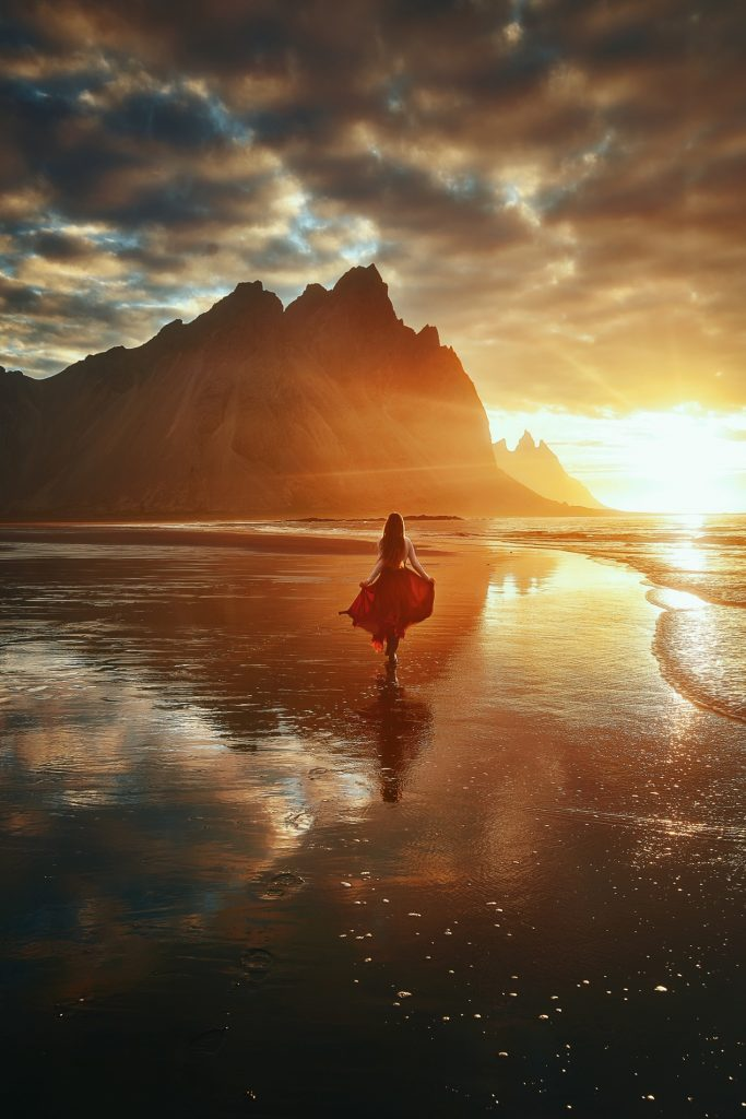 woman prancing towards sharp Vestrahorn mountains during golden hour