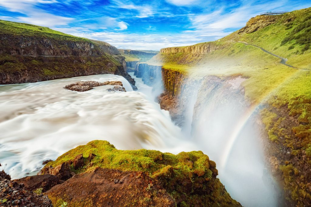 rainbow over gullfoss waterfall on a sunny day with blue sky