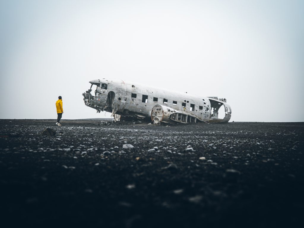 man in yellow looking at plane wreck on black sand best things to do in Iceland