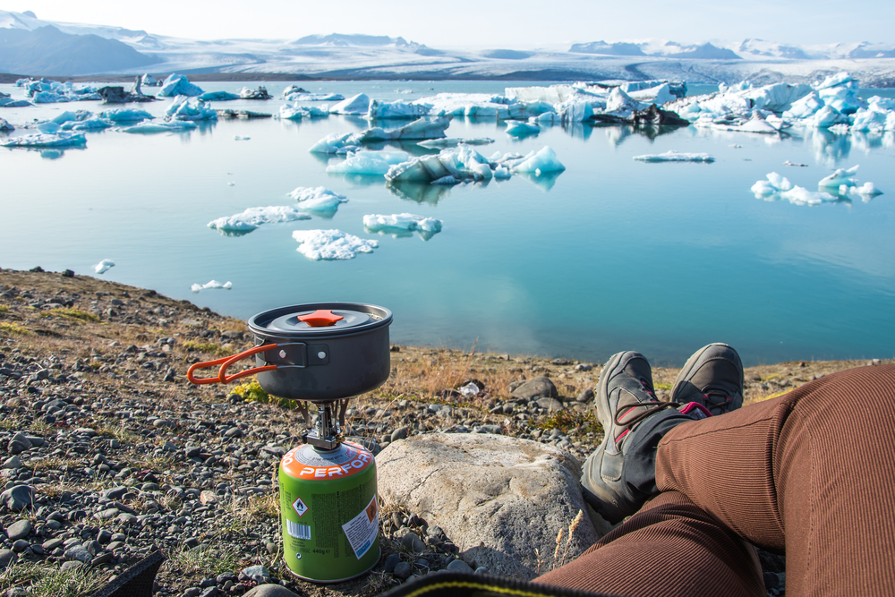 Camping in Iceland with a camp stove near glacial lagoon.
