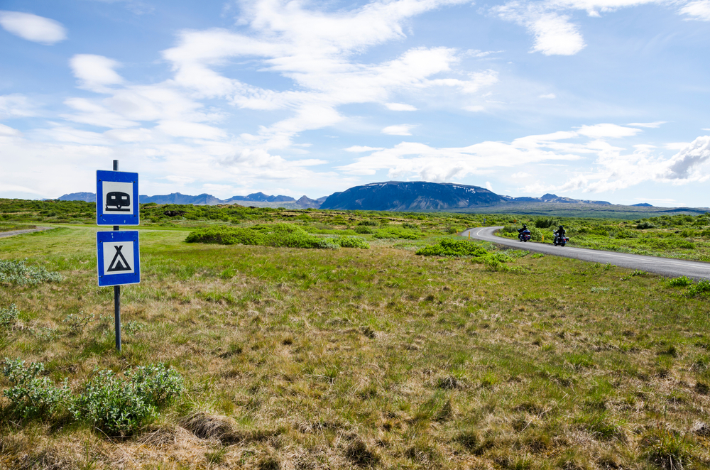 Landscape with road sign for camping in Iceland.