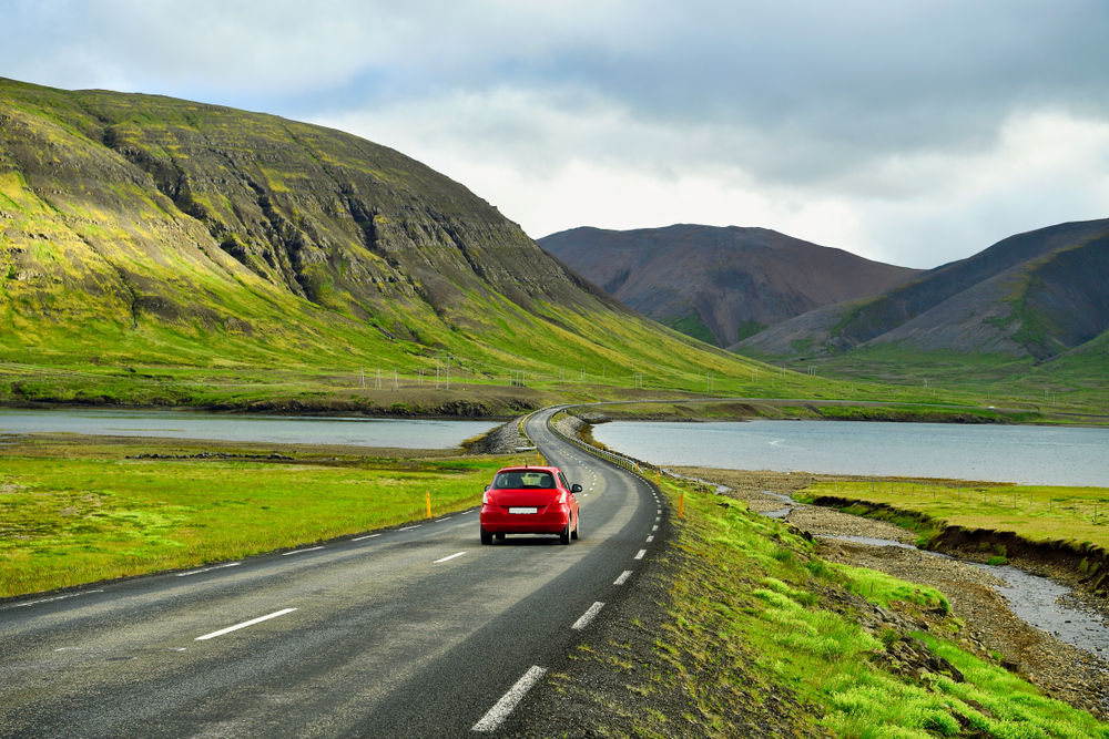 Car driving down road in Iceland showing how to get around while camping in Iceland.