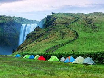 A line of tents for camping in Iceland near the Skogafoss Waterfall.