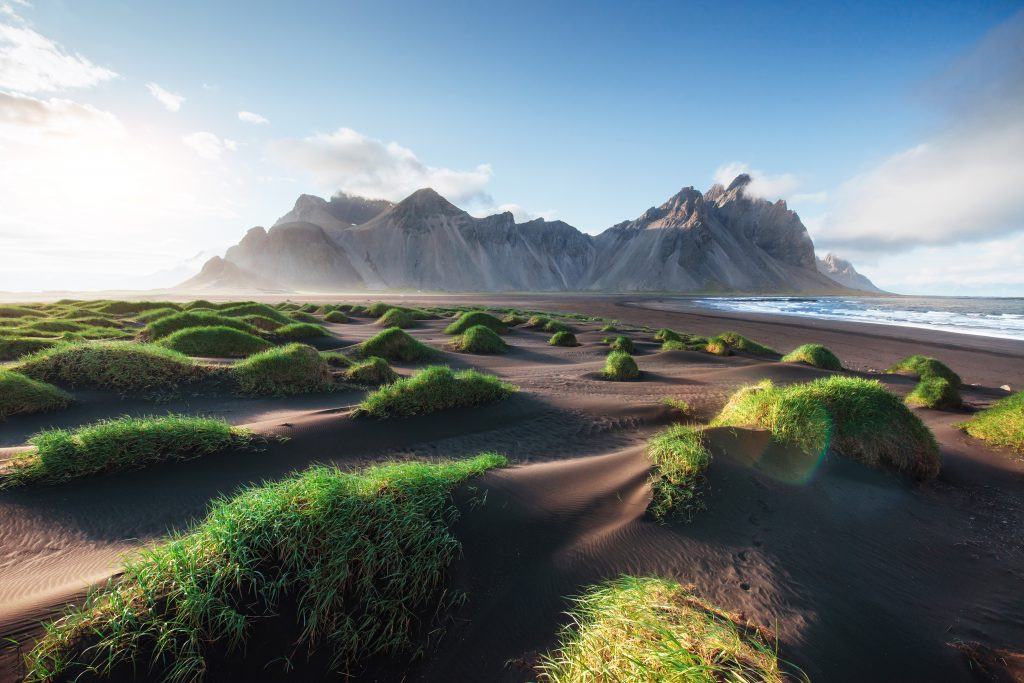Photo of mountains and volcanic lava sand dunes on the beach in Stokksness, Iceland.