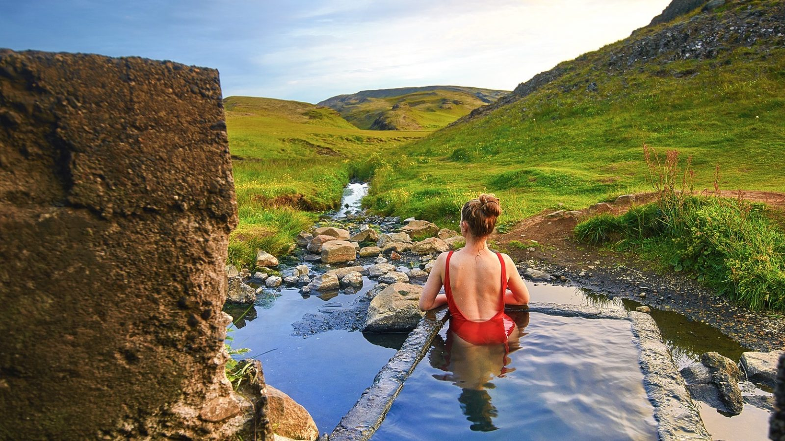 woman in Hrunalaug hot springs at sunset