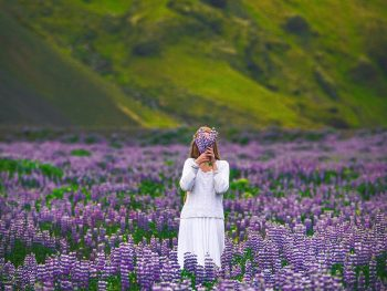 girl holding flowers on the side of the road for her iceland itinerary