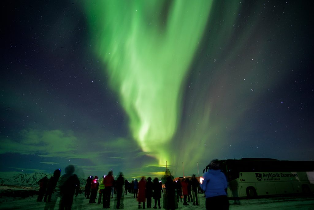 people standing in front of northern lights Iceland northern lights tours