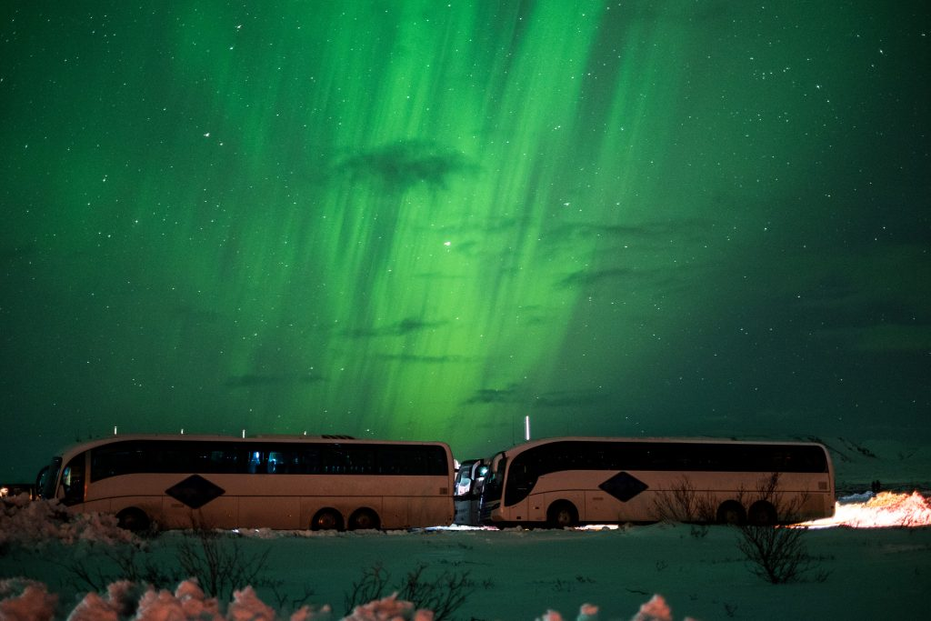 two buses in front of aurora borealis