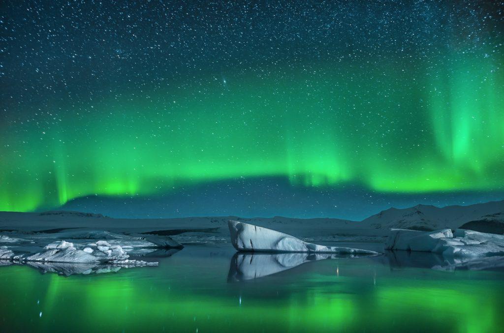 aurora borealis reflecting on glacier lake
