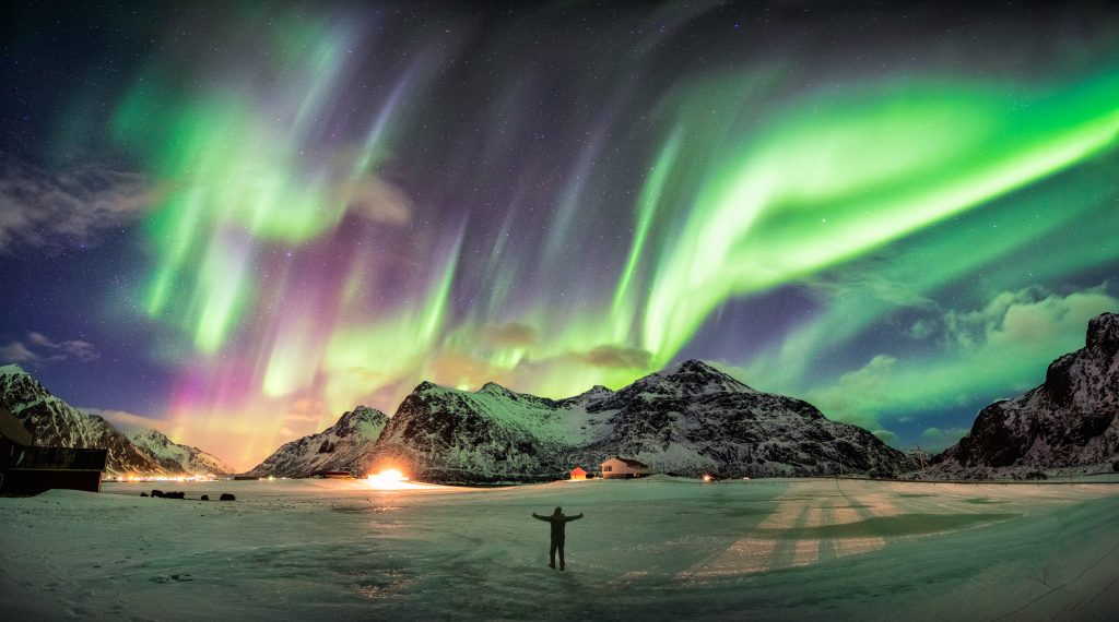 Man in snow covered mountains embracing northern lights