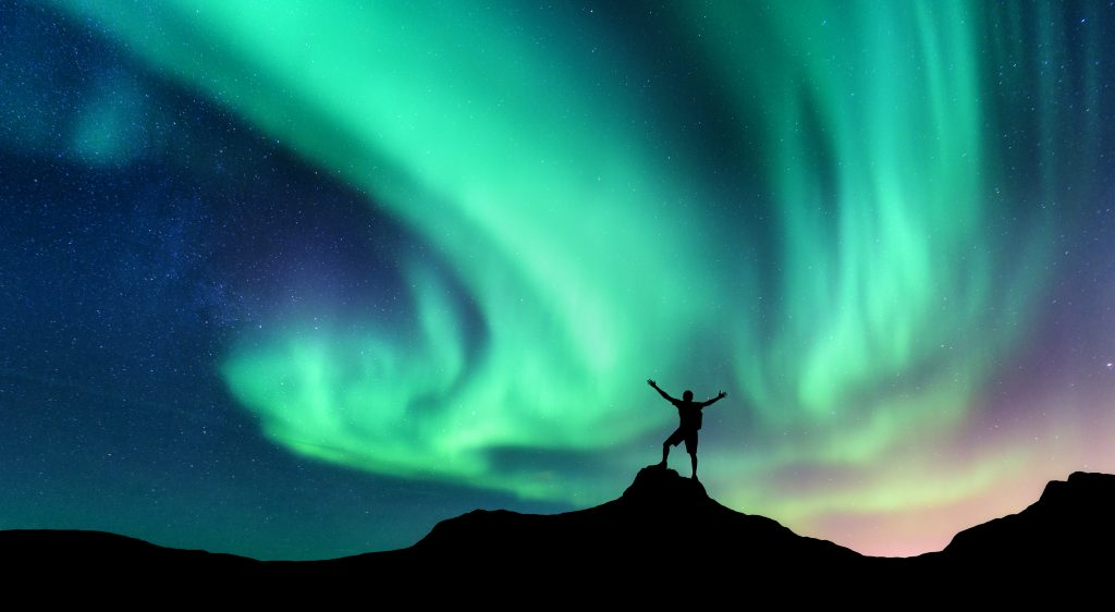 silhouette of a man standing in front of teal northern lights Iceland northern lights tours