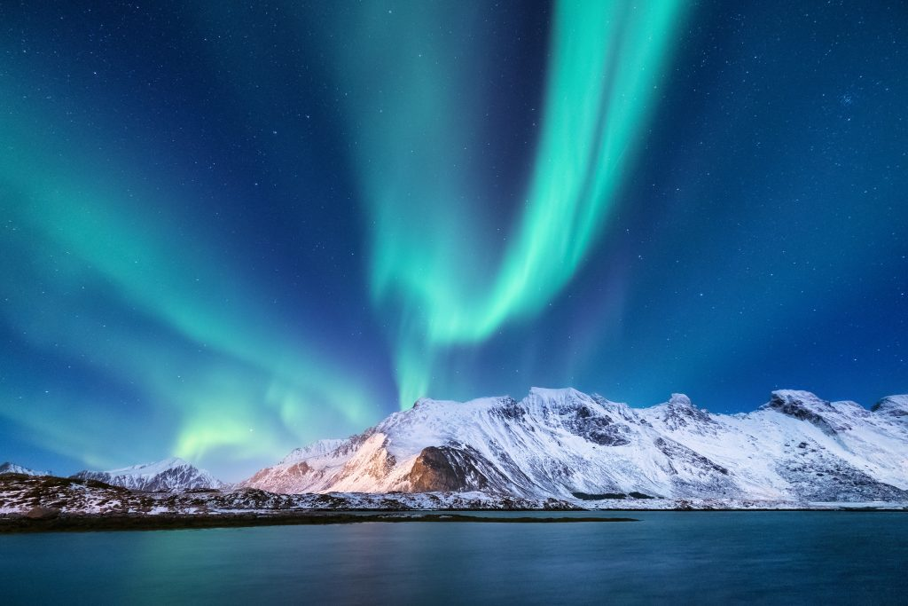 snow capped mountains framed by blue aurora borealis streaks