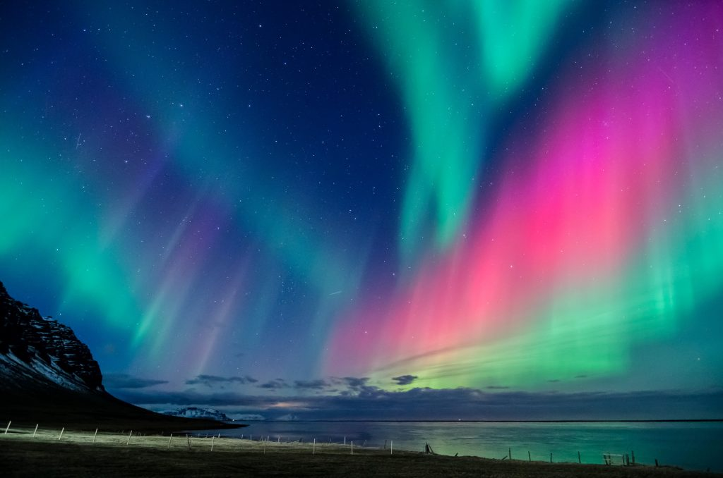 northern lights with teal and red streaks Iceland northern lights tours