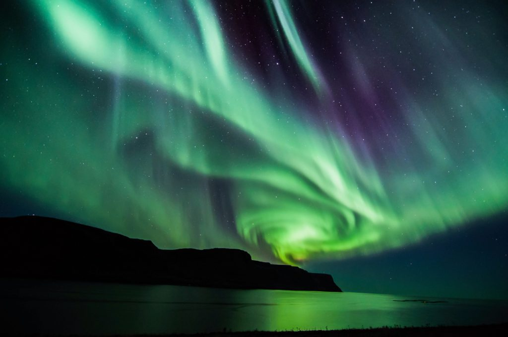 dark cliffs contrasted by swirling northern lights Iceland northern lights tours
