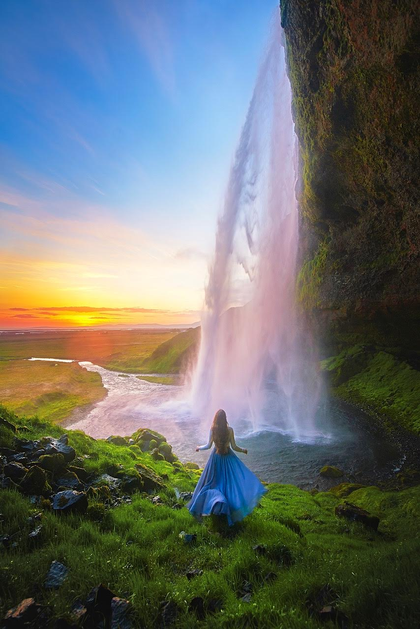Women standing in front of Seljalandsfoss at sunrise