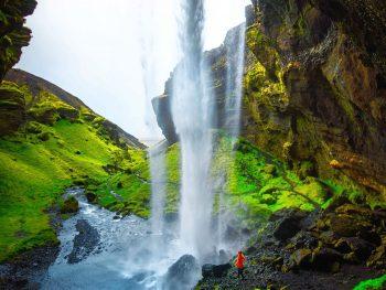 walking behind Kvernufoss Waterfall