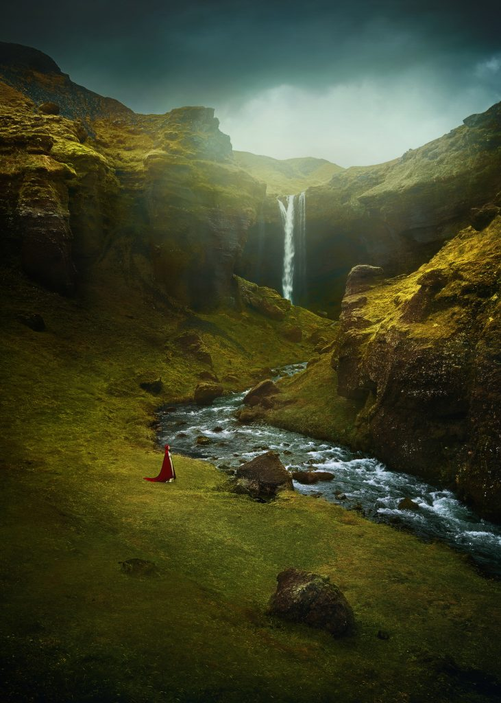 fine art photography of mystical photo of a woman standing in a cape at Kvernufoss Waterfall