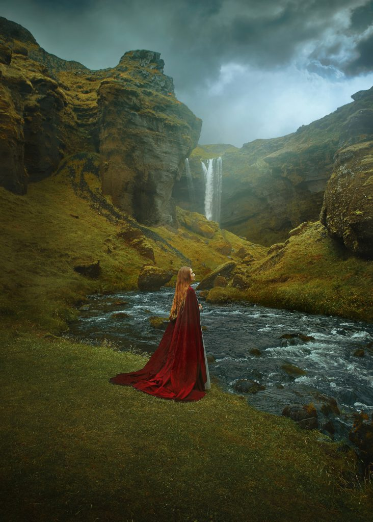 close up image of a woman wearing a cape at Kvernufoss Waterfall in Iceland