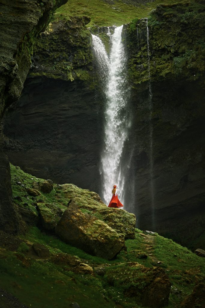 close up image of a woman at Kvernufoss Waterfall in a red skirt